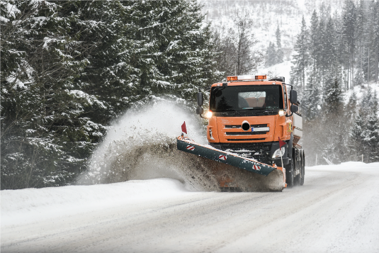 Snow plow clearing a wintry road
