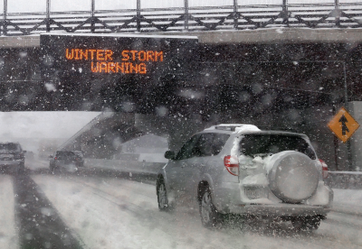 Car driving on an icy road with a winter storm warning