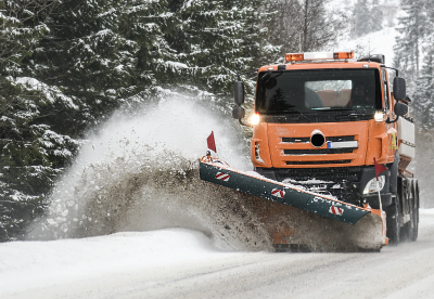 Snow plow driving along an icy road